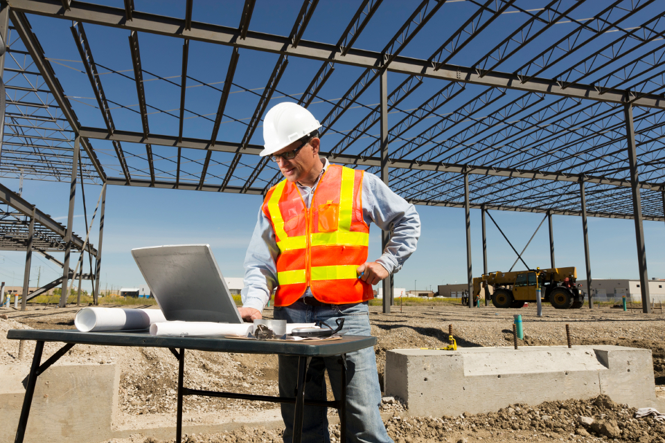 Man Using a Laptop at Construction Site | Kern County Builders' Exchange (KCBEX) | Bakersfield, CA