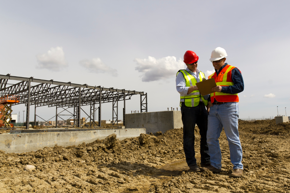 Two Men Reading a Clipboard Smiling | Kern County Builders' Exchange (KCBEX) | Bakersfield, CA